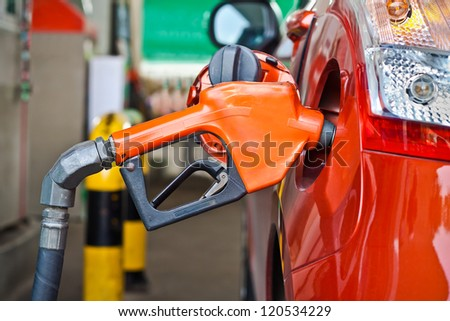 Closeup of a fueling hose at a gas station. - stock photo