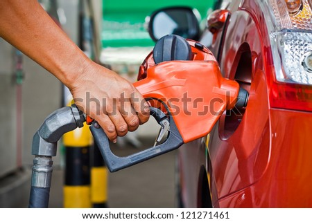 Closeup of a fueling hose at a gas station with a Hand - stock photo