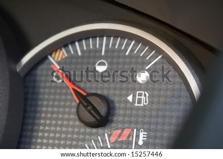 Closeup of a gas gage displaying that the car has an empty tank.  Shallow depth of field. - stock photo