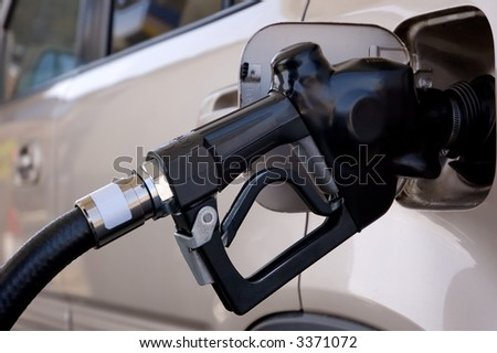 Closeup of a gasoline pump nozzle in the tank of an SUV