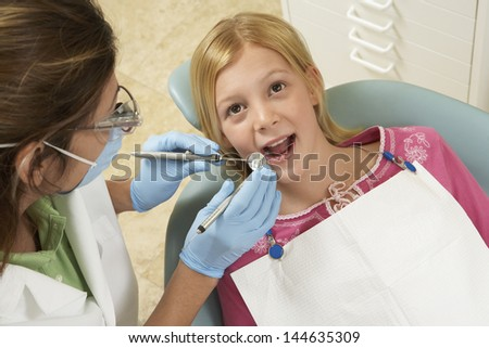 Closeup of a girl having her teeth examined at the dental clinic - stock photo