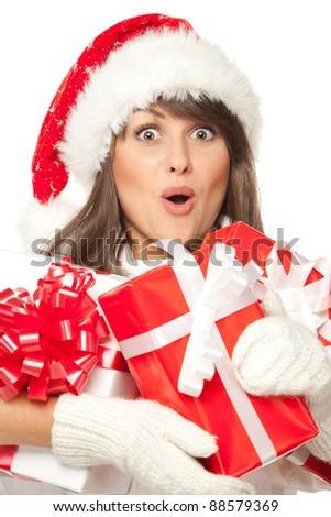 Closeup of a girl in Santa hat, surprised by having received a lot of Xmas presents, over white background - stock photo