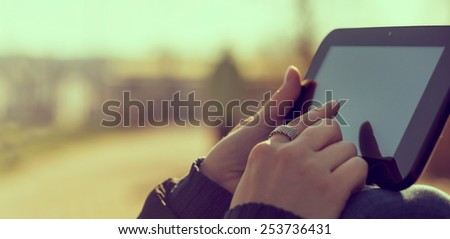 Closeup of a girl using tablet in the park - stock photo