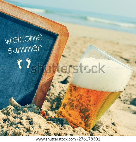 closeup of a glass of refreshing beer and a chalkboard with a wooden frame and the text welcome summer written in it, placed on the sand of a beach - stock photo