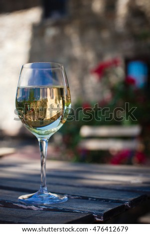 Closeup of a glass of white wine with the background of antique Tuscany winery