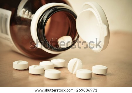 Closeup of a Glass Prescription brown bottle with pills - stock photo