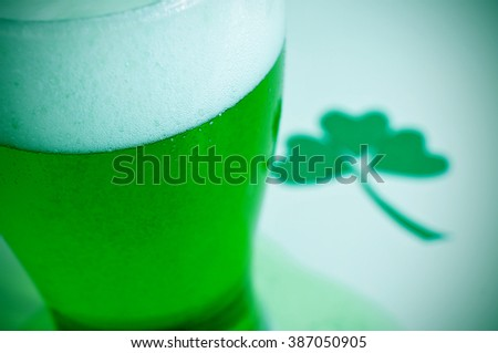 closeup of a glass with dyed green beer and a three-leaved shamrock in the background, for saint patricks day - stock photo