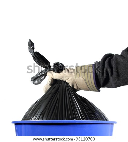 closeup of a gloved hand taking a trash bag out of a blue container - stock photo