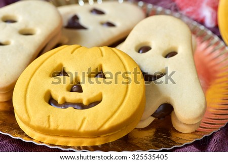 closeup of a golden tray with a pumpkin-shaped cookie and some other ghost-shaped cookies