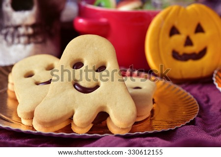 closeup of a golden tray with some ghost-shaped cookies and a pumpkin-shaped cookie, a bowl with halloween candies and a scary skull in the background