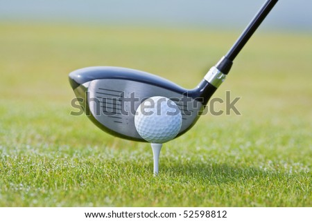 closeup of a golf ball and club on green grass - club out of focus - stock photo