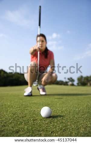 Closeup of a golf-ball with a woman lining up her putt in the background. Vertical shot. - stock photo
