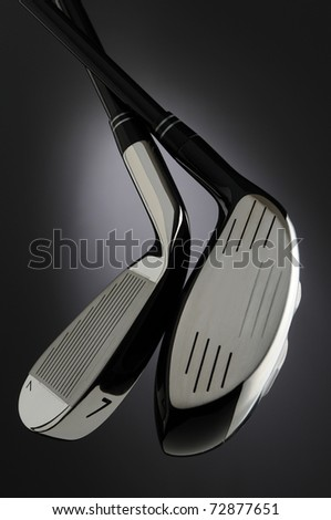 Closeup of a Golf Driver and seven iron over a dark background with spot-light highlight in the center. Vertical Composition - stock photo