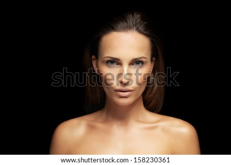 Closeup of a gorgeous young woman with perfect healthy skin isolated on black background. Natural Beauty with fresh and clean skin - stock photo