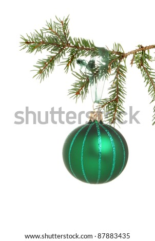 Closeup of a green Christmas bauble hanging from a branch of a Christmas tree