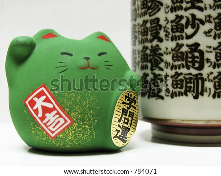 Closeup of a green Feng Shui cat with Japanese Kanji writing, brings academic strength. - stock photo