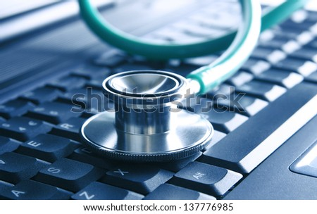 Closeup of a green stethoscope lying on a blue notebook keyboard (selective focus) - stock photo