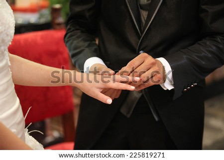 Closeup of a groom putting the ring on his bride's finger on their wedding day - stock photo