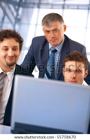 Closeup of a group of business people working on laptop with their manager at the office. - stock photo