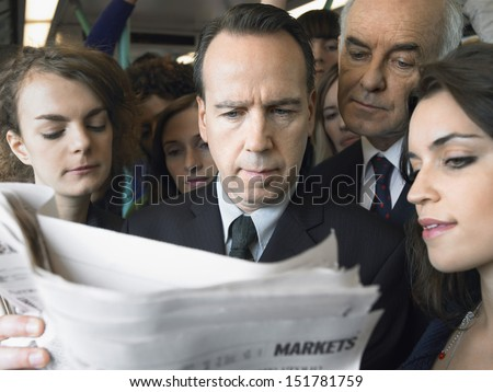 Closeup of a group of commuters reading newspaper in train - stock photo