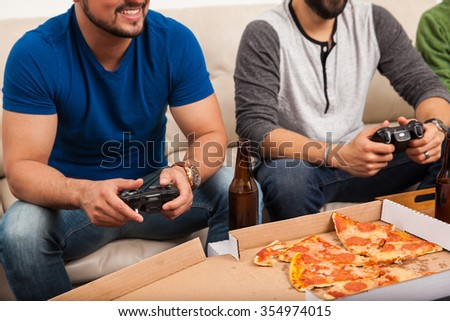 Closeup of a group of male friends playing videogames with pizza and beer at home - stock photo