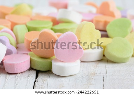 Closeup of a group of pastel candy Valentine's hearts on a rustic white wood table. Horizontal format. - stock photo