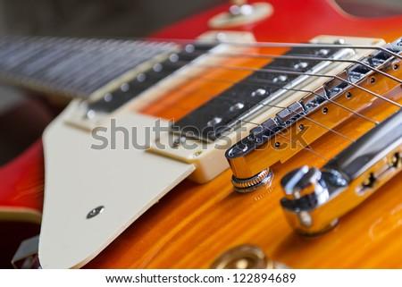 closeup of a guitar bridge with control knobs - stock photo
