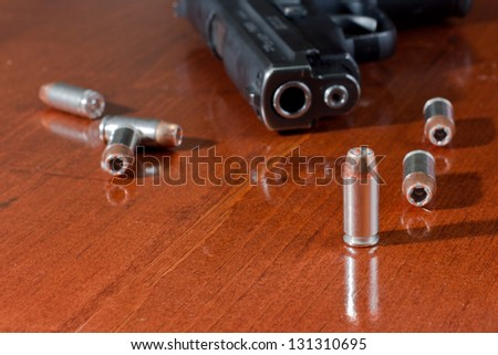 closeup of a hallow point bullet with a gun on a table - stock photo