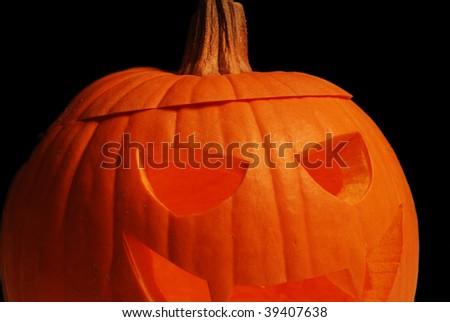 Closeup of a Halloween Jack-o'-Lantern against a black background - stock photo