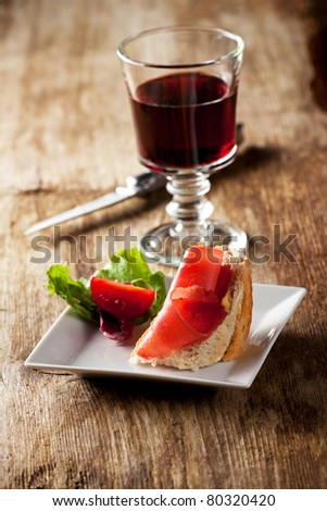 closeup of a ham sandwich and red wine