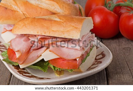 Closeup of a ham sandwich with cheese, lettuce and tomato