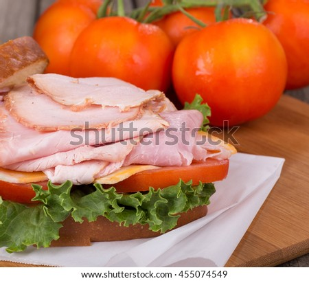 Closeup of a ham sandwich with cheese, tomato and lettuce