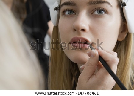 Closeup of a hand applying lipstick to female model's lips