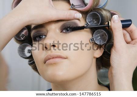 Closeup of a hand applying mascara to female model - stock photo