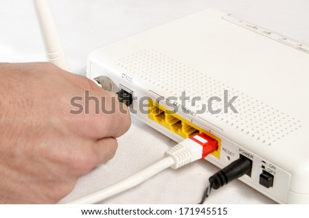 closeup of a hand connecting a modem for high speed internet