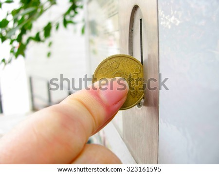 Closeup of a hand dropping a coin into a vending machine slot  - stock photo