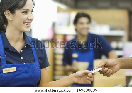 Closeup of a hand giving female employee loyalty card in supermarket - stock photo