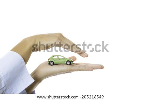 closeup of a hand holding a toy car isolated on a white background - stock photo