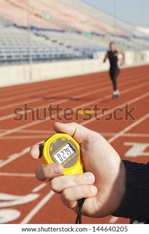 Closeup of a hand holding stopwatch with blurred female runner on the race track