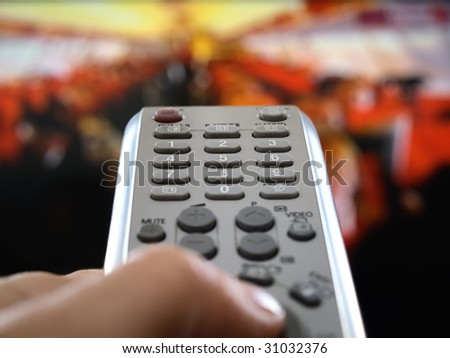 closeup of a hand  holding the remote control in front of the television, shallow DOF, conceptual image of the world under control - stock photo