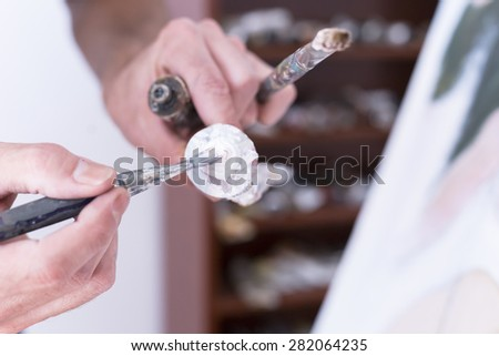 closeup of a hand of a painter taking paint with a paintbrush from a paint tube - focus on the paintbrush - stock photo
