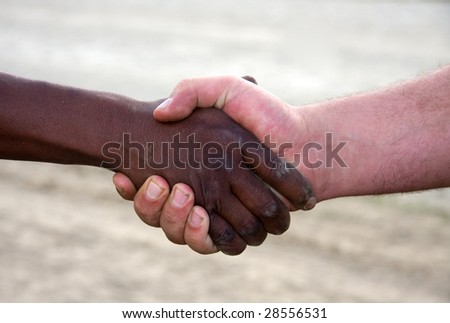 closeup of a hand shake,interracial between black and white. Dusty,dirty hands outdoors, - stock photo
