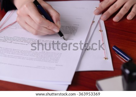 Closeup of a hand signing atestament by a pen.