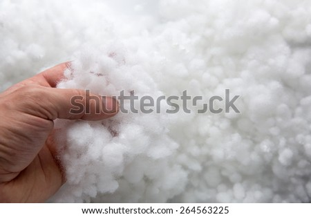 Closeup of a hand taking synthetic filler - stock photo
