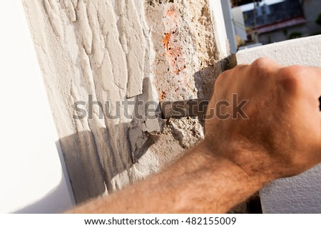 Closeup of a hand with a chisel worker in breaking the plaster.  Focus on the tip of the working tool.