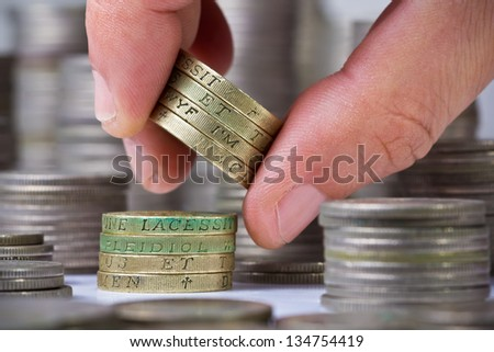 Closeup of a hand withdraws british pound coins from the stack - stock photo