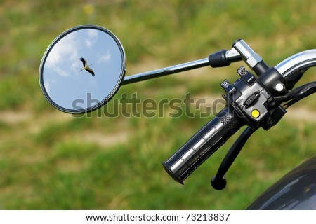 Closeup of a handlebar of a vintage motorbike with a flying stork reflected in its mirror. - stock photo