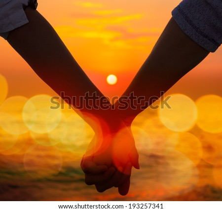 Closeup of a Hands of a Couple Held Together on the Background of Sea Sunset. Toned Instagram Styled Photo with Bokeh. Romantic Summer Travel Concept. - stock photo