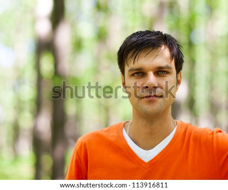 Closeup of a handsome casual young man outdoor looking at the camera - stock photo