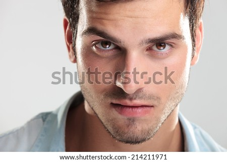 Closeup of a handsome man in blue shirt, looking at the camera - stock photo